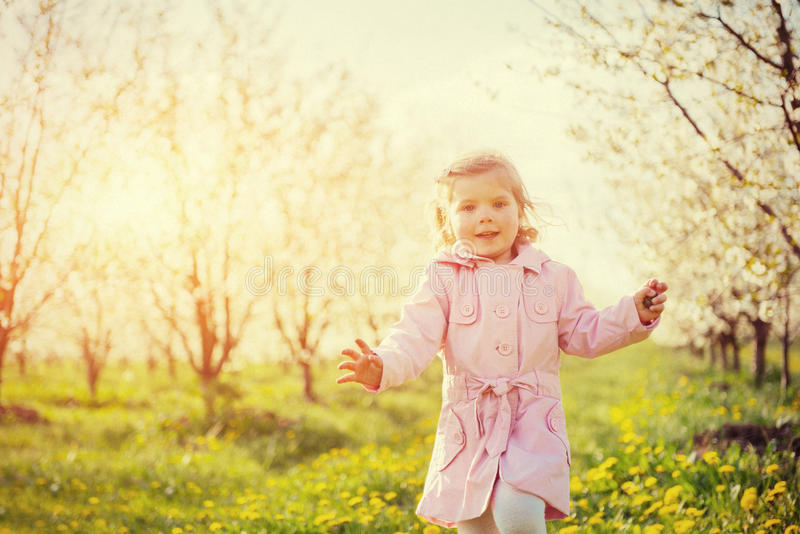 Child running outdoors blossom trees. Colorful toning effect stock images