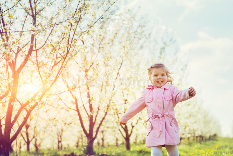 Child running outdoors blossom trees. Colorful toning effect royalty free stock image