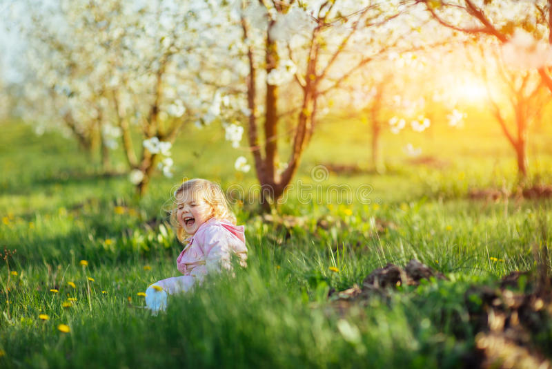 Child running outdoors blossom trees. Colorful toning effect royalty free stock photos