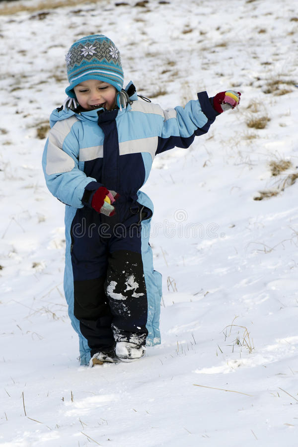 Child running in snow. Happy child running in snow in field outdoors stock photo