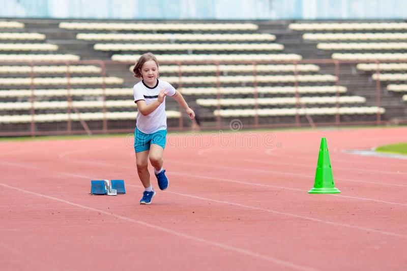 Child running in stadium. Kids run. Healthy sport. Child running in stadium. Kids run on outdoor track. Healthy sport activity for children. Little girl at royalty free stock image