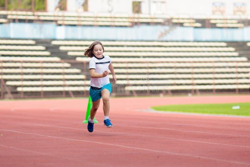 Child running in stadium. Kids run. Healthy sport stock photo