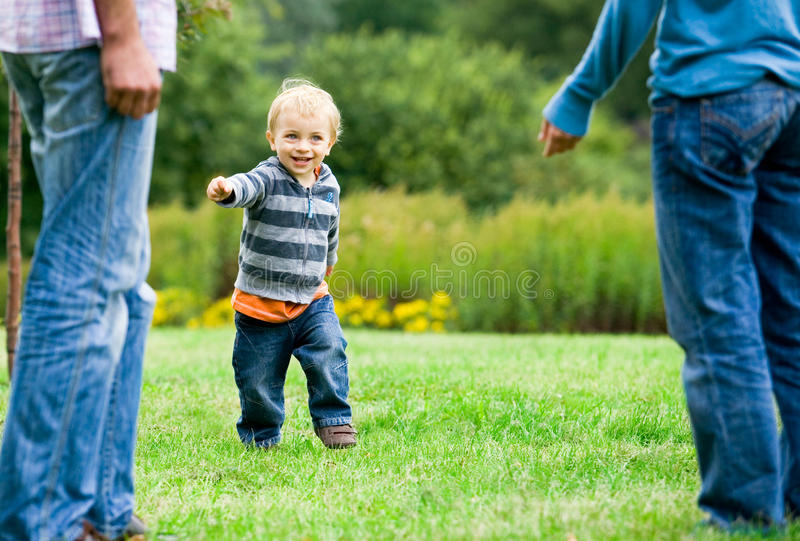 Child running to parents. In park stock images