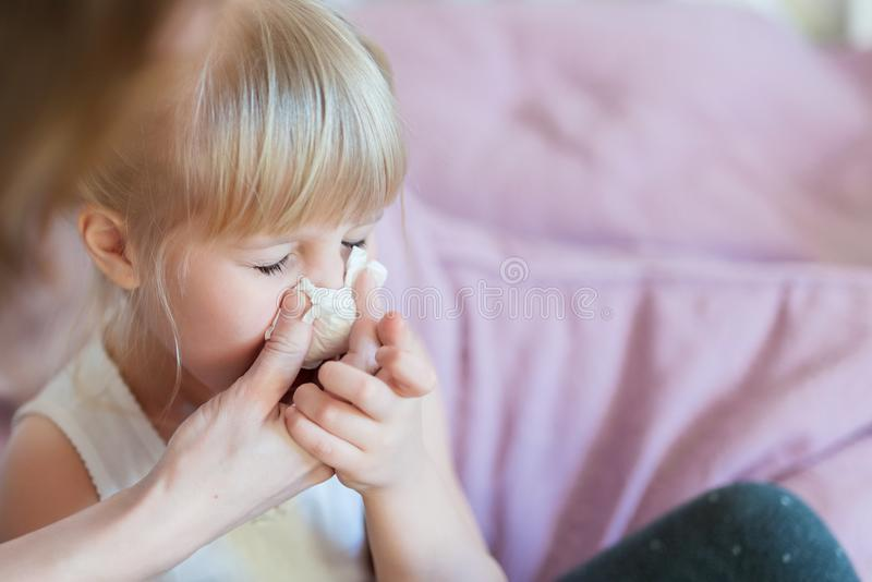 Child with runny nose. Mother helping to blow kid`s nose with paper tissue. Seasonal sickness.  royalty free stock image