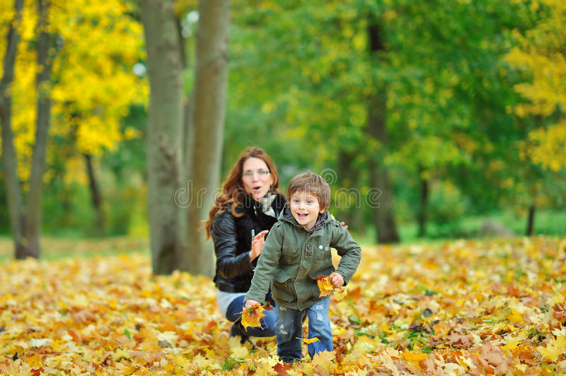 Child runs away from mother while plaing in a park. Child runs away from his mother while plaing in a park stock photos