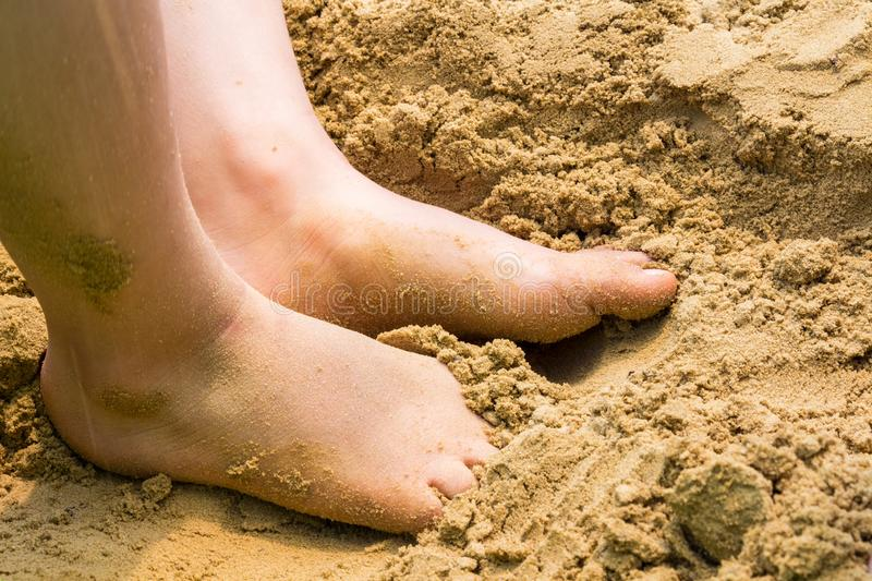 Child`s bare feet in sand at beach stock photo