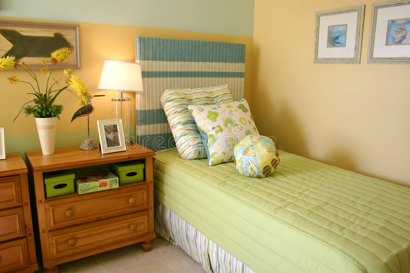 Child's Bedroom. Decorative child's bedroom with lime green and aqua bedspread, headboard and pillows, soft yellow walls and cherry chests