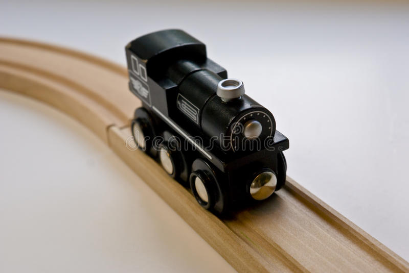 Child's black wooden toy train on wood tracks royalty free stock image