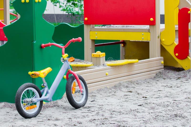 Child& x27; s-cykeln står på sanden på en lekplats arkivfoto