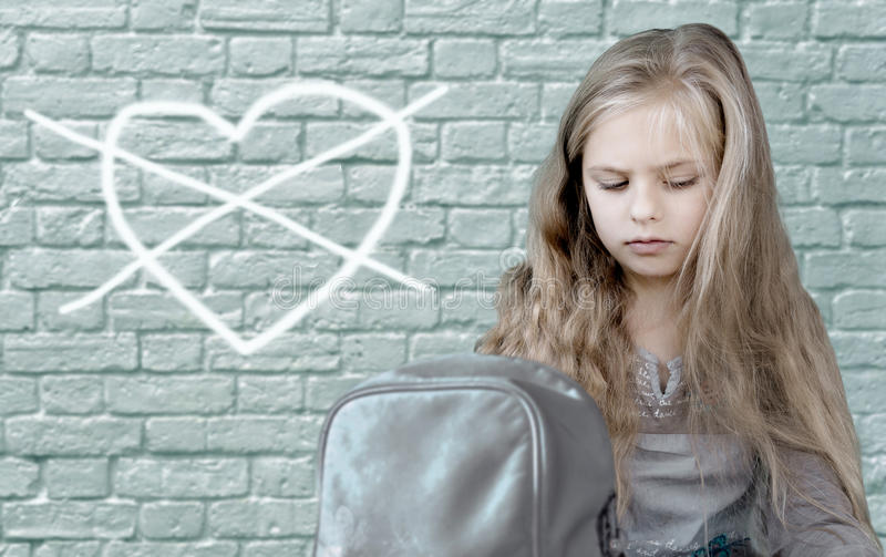 Child's drawing. Pretty sad girl sitting on background of brick wall, which is painted the heart crossed stock photography