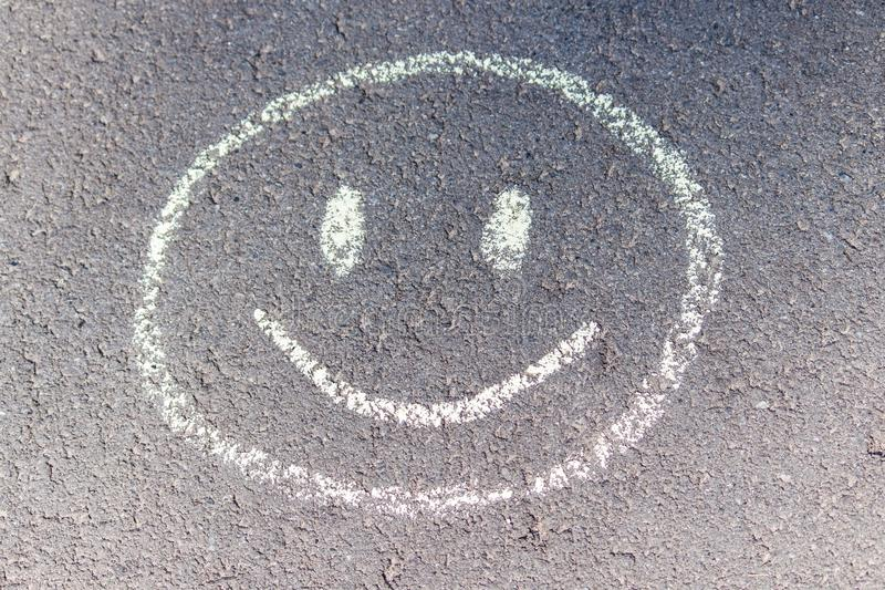 Child`s drawing of a smile on asphalt. Good day with good moon. royalty free stock photos