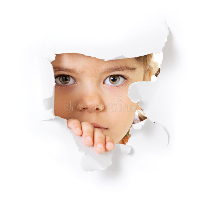 Child's face looking through a hole in paper. Face of the child looking through a hole in the white paper royalty free stock images