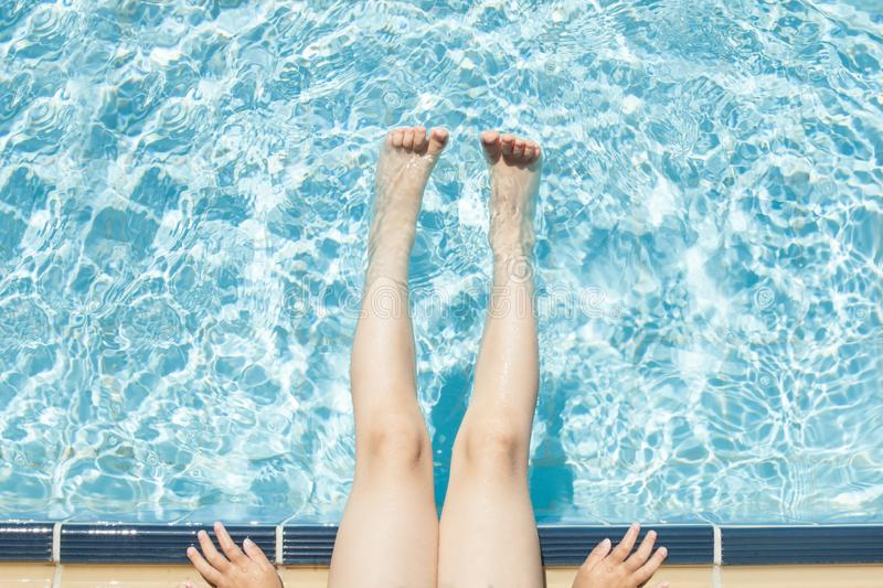 Child`s feet in blue pool water. Fun summertime outdoor activity of swimming stock images