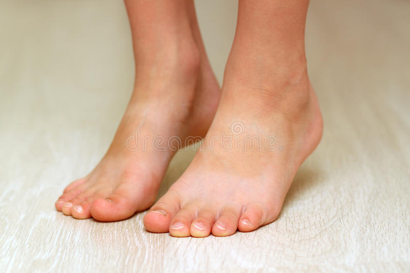 Child& x27;s feet on parquet laminate wooden texture floor close-up. royalty free stock image