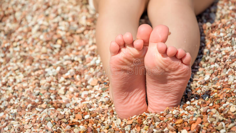 Child's feet on the pebbles beach royalty free stock photography