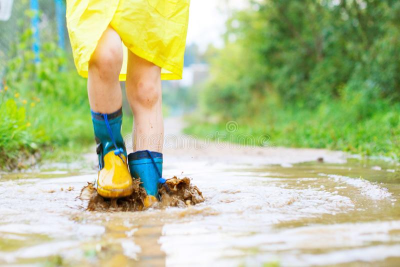 Child`s feet in a rubber boot. In a puddle royalty free stock images