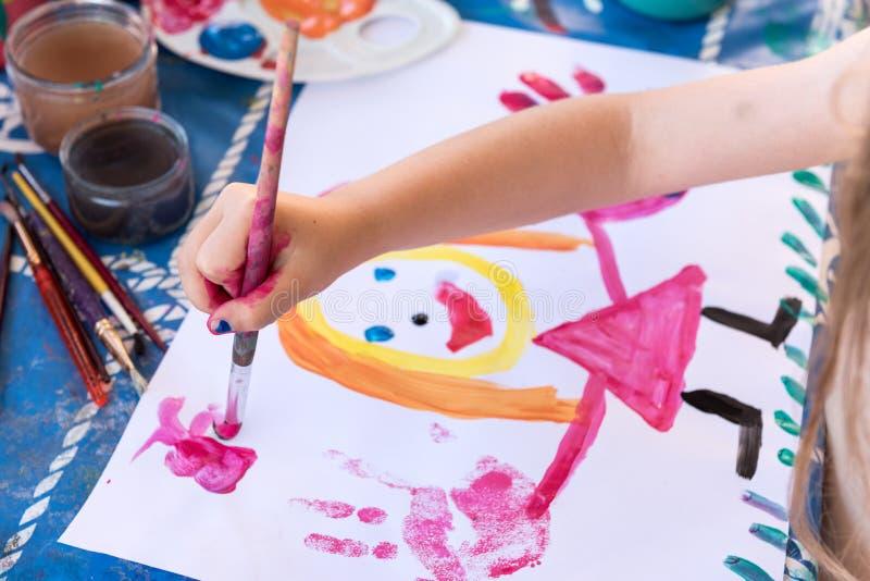 Child`s finger painting. Little girl having fun painting her hands stock image