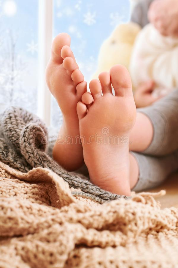 Free Child`s Foots Are On A Window Sill With Wool Plaid And Yarns Stock Image - 134876041