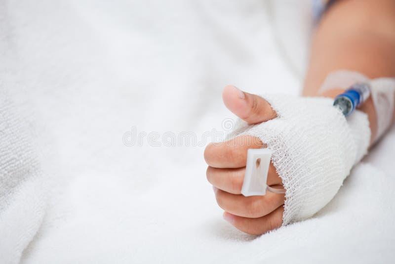 Child& x27; s geduldige hand met zoute intraveneus & x28; iv& x29; druppel stock afbeelding