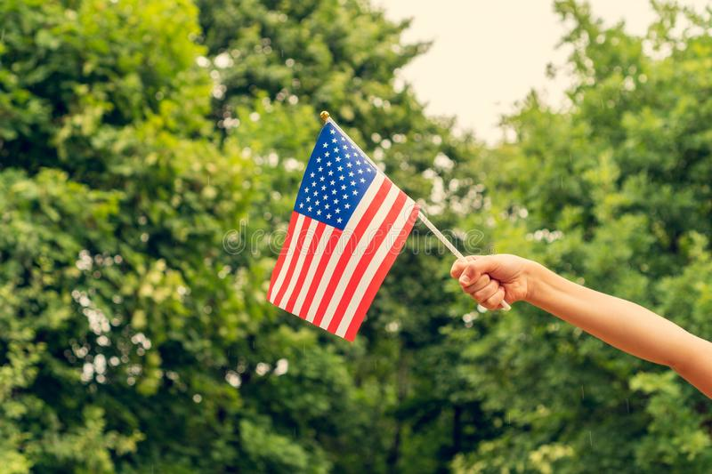 Child`s hand with american flag. Outdoors on summer day. Independence Day concept stock photography