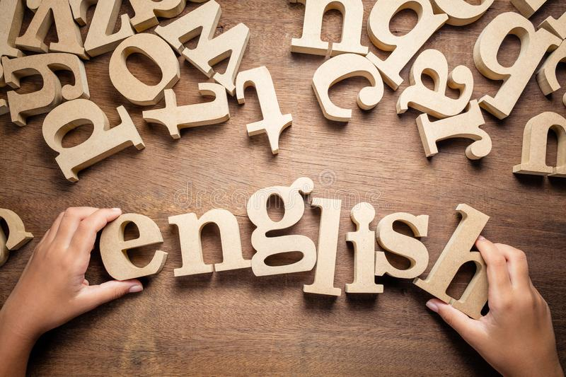 Child`s Hand Arrange English Word. Closeup child`s hand arrange wooden alphabets on the table as English word royalty free stock photography