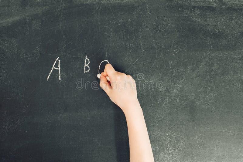 Child`s hand with chalk write alphabet on black chalkboard stock image