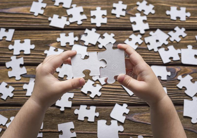 Baby hand collects pieces of the puzzle. A child`s hand collects a puzzle on a wooden background royalty free stock photography