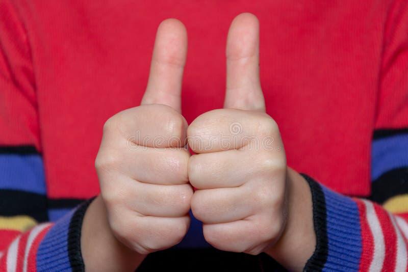 Child& x27; s hand die duim, tonen als, positief teken stock afbeelding