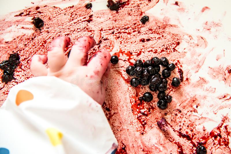 Child`s hand while eating berries stock photos
