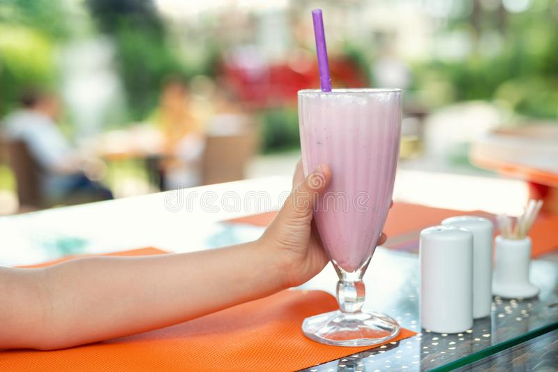 Child`s hand holding big glass with fresh tasty strawberry milkshake coctail at cafe outdoors. Children healthy diet and. Child`s hand holding big glass with royalty free stock image
