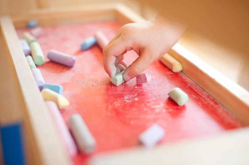 Child`s hand holding chalk is about to draw in the talent classroom stock photo
