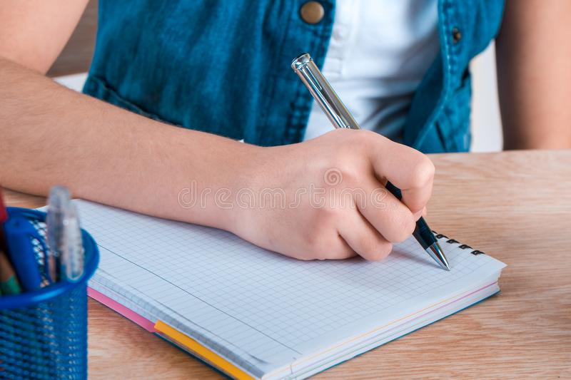 Child`s hand holding pen. The child writing letters in a noteboo. K stock photography