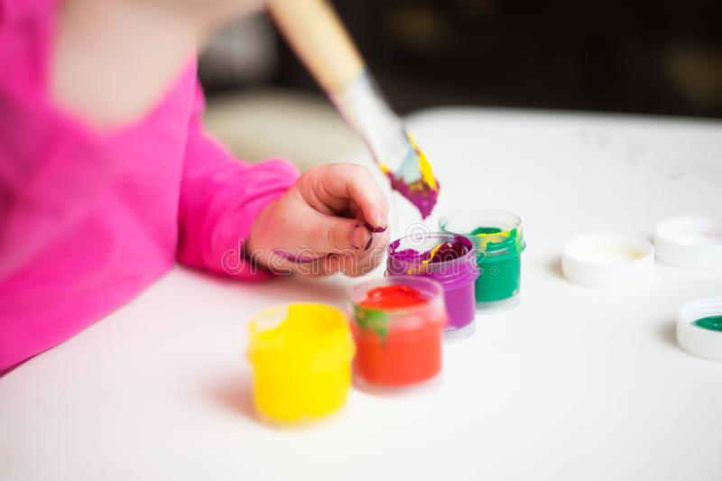 Child`s hand holds paint brush. stock photography