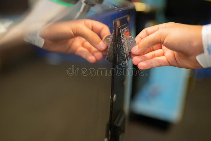 Child`s hand inserting a quarter into the machine stock photos