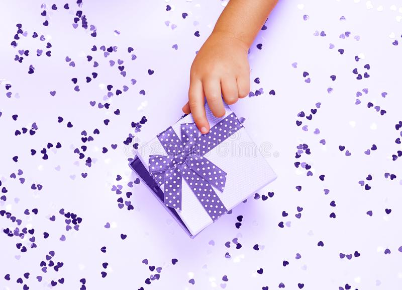 Child`s hand opening gift box on pinh background with heart shaped confetti. Top view, flat lay. ultra violet style royalty free stock images