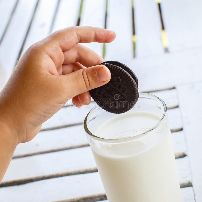 Child's hand with Oreo cookies extends to milk royalty free stock photography