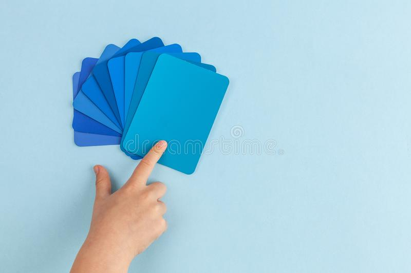 Child`s hand pointing at color samples cards. stock photo