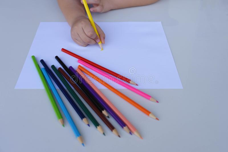 The child`s hand preparing to write on a white sheet of paper with colored pencils.  Education and children activities concept.  stock photo