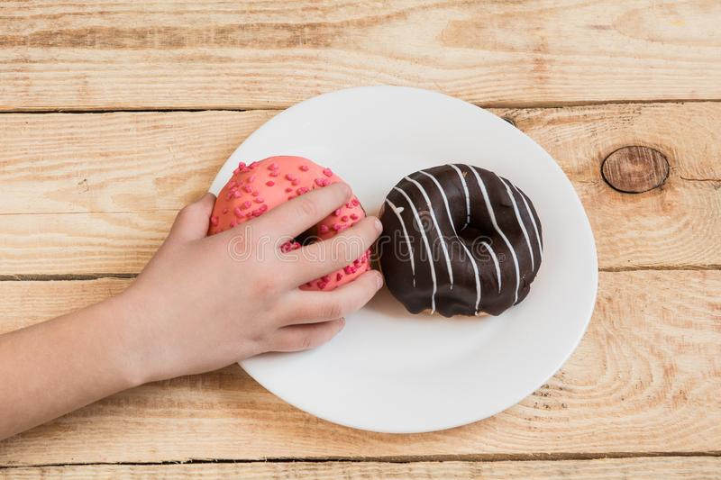 Child`s hand reaches donuts. Tasty food for kids. having fun with doughnut royalty free stock images