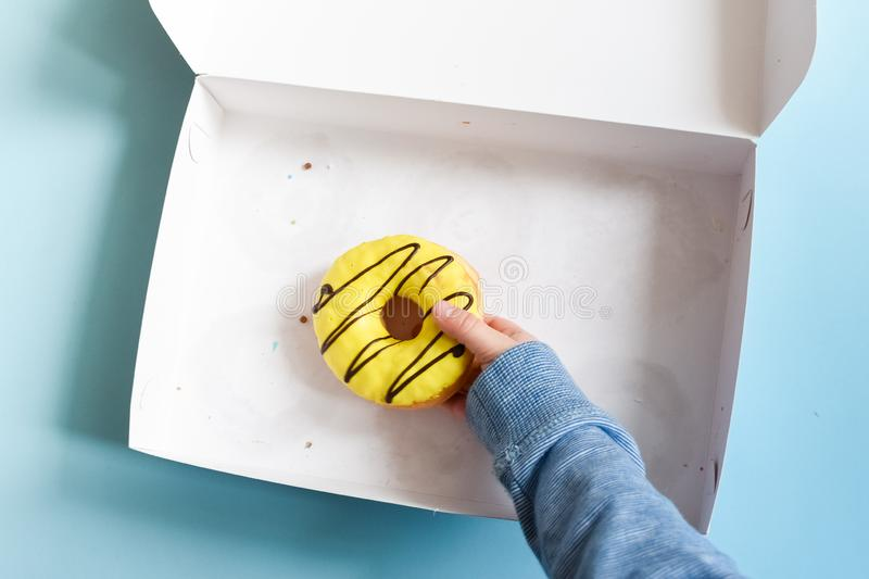 Child`s hand reaching to grab doughnut. Donut box with a young male child`s hand reaching to grab the last yellow banana frosted doughnut over blue background royalty free stock photo