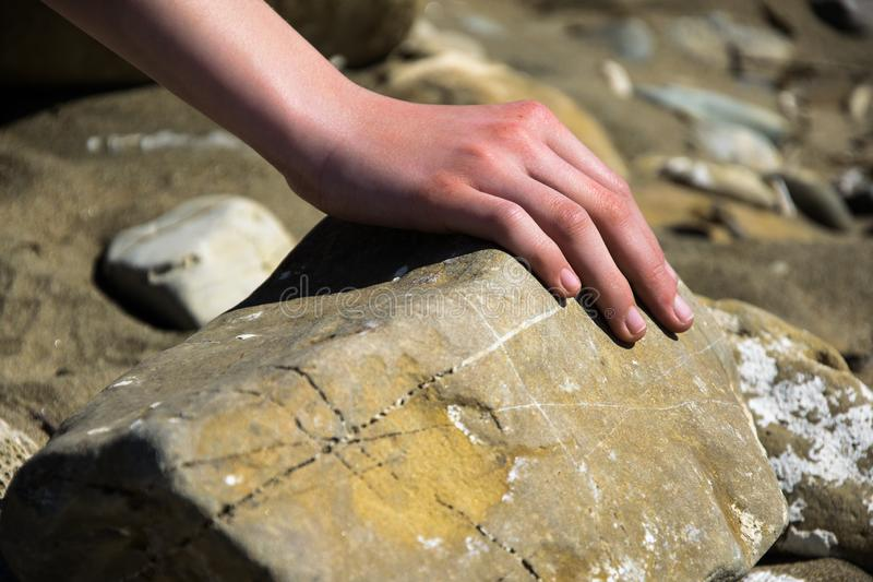 Hand on stone, the hardness of stone. A child`s hand rests on a stone on a beach, a symbol of natural hardness stock photos