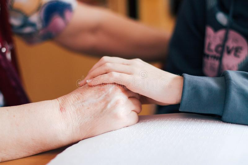 Child`s hand on top of a senior woman`s hand royalty free stock image