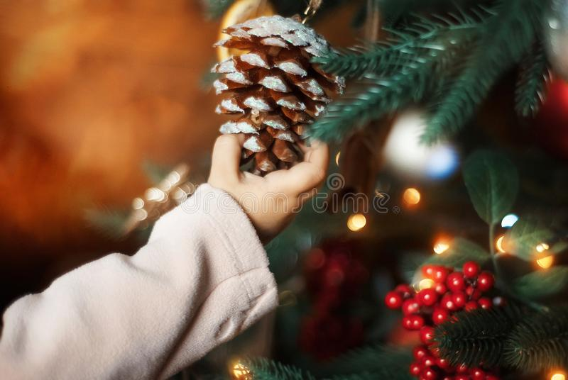 Child`s hand touches decorative brown and white cone on decorated with lights christmas tree. Close up. stock photo