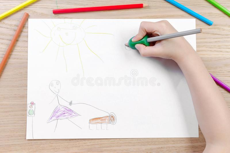 Child`s hand with writing tool for help by incorrect holding of pencil. Closeup stock photo