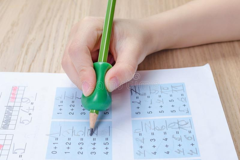 Child`s hand with writing tool for help by incorrect holding of pencil, homewortk, math. Child`s hand with writing tool for help by incorrect holding of pencil stock photos