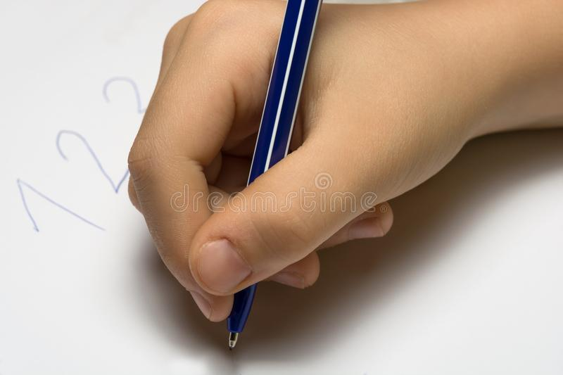 Child`s hand writing on a white sheet of notebook.  stock images