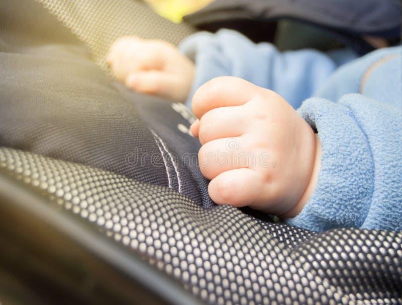 Child& x27; s-handnäven, selektiv fokus, barnet är i sittvagnen, medan gå utomhus, närbilden fotografering för bildbyråer