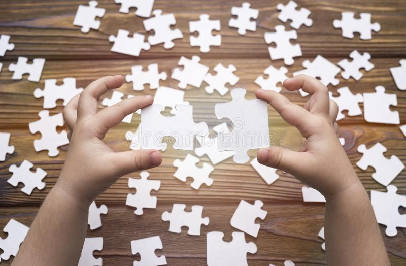 The child`s hands collect puzzles, docking two parts. royalty free stock photos