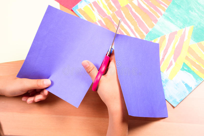 Child`s hands cutting colored paper with scissors. Kid`s hands cutting colored paper with scissors stock images