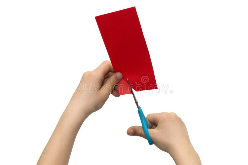 Child`s hands cutting colored red paper with scissors isolated o royalty free stock photography